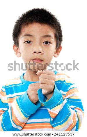 smiling little boy raised his hands up. shooting in the studio - stock photo