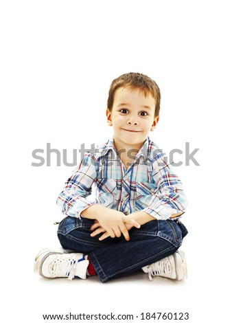 Smiling little boy sitting down on floor in jeans.  Isolated on white background  - stock photo