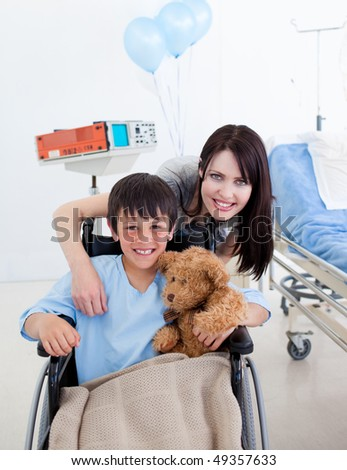Smiling little boy sitting on wheelchair and his mother at the hospital - stock photo