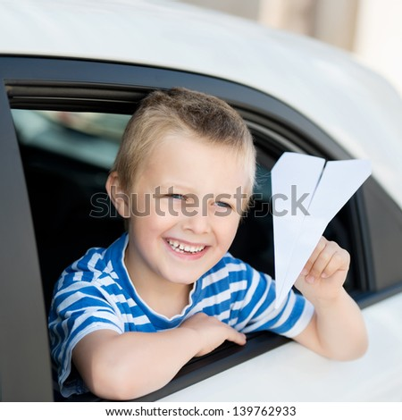 Smiling little boy throwing a paper plane while looking out the car - stock photo