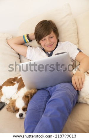 Smiling little boy watching laptop - stock photo