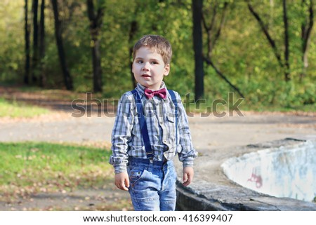 Smiling little boy with bow tie and jeans poses in sunny green park - stock photo
