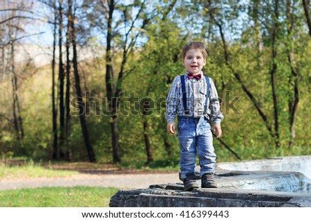 Smiling little boy with bow tie and jeans stands in sunny green park - stock photo