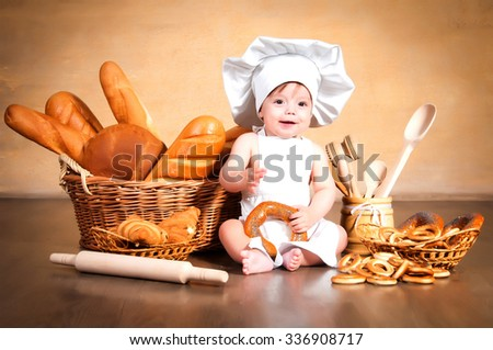 Smiling little cook in a chef's hat sitting beside wicker baskets of pastries and bakery products - stock photo