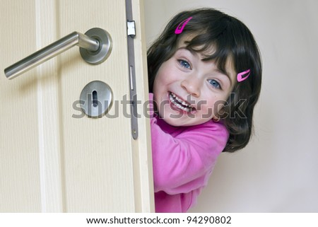 Smiling little enjoys girl is hiding behind a door - stock photo