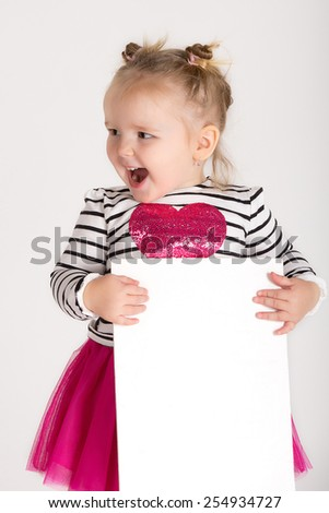 Smiling little girl behind empty white board - stock photo