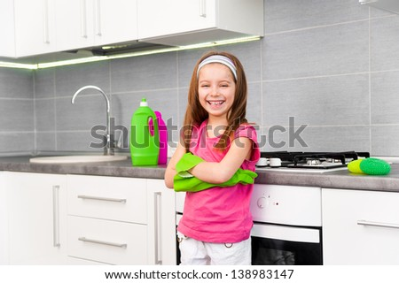 smiling little girl cleans in the kitchen at home - stock photo