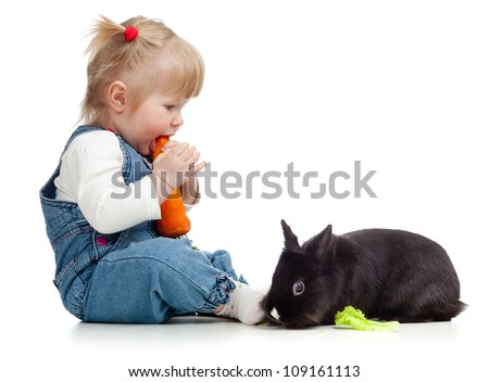 Smiling little girl eating a carrot and feeding rabbit - stock photo