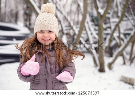 Smiling little girl enjoyig winter at home - stock photo