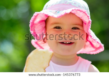 Smiling little girl feeding birds - stock photo