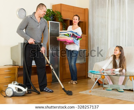 Smiling little girl helping happy parents to clean at living room. Focus on man - stock photo