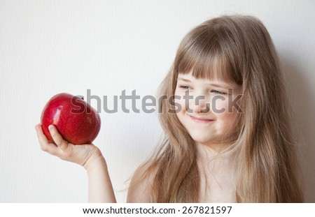 Smiling little girl holding a big red apple - stock photo