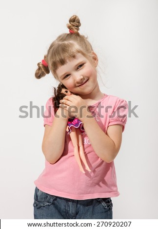 Smiling little girl holding a doll in a studio - stock photo