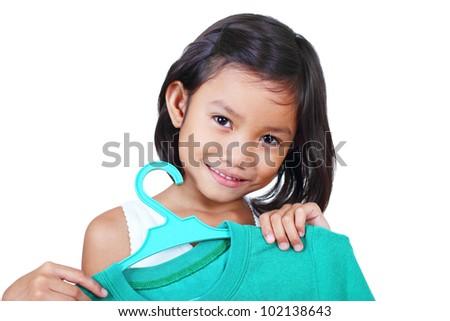 Smiling little girl holding a shirt in hanger. - stock photo