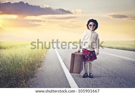 Smiling little girl holding a suitcase on a country road - stock photo
