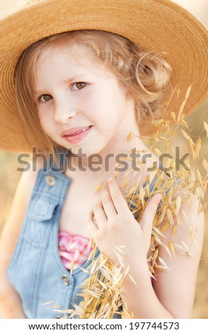 Smiling little girl holding dry grass, wearing straw outdoors - stock photo