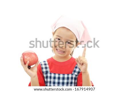 Smiling little girl holding fruit - stock photo