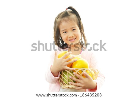 Smiling little girl holding fruit - stock photo
