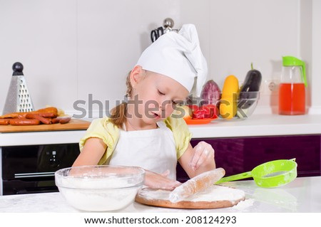 Smiling little girl in a chefs uniform standing at a kitchen counter rolling out her dough as she learns to bake biscuits - stock photo