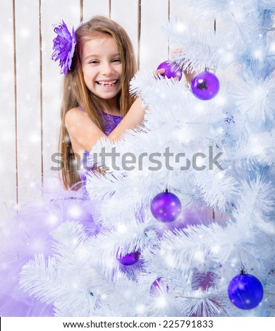 smiling little girl in a lilac dress decorated white Christmas tree purple balls - stock photo