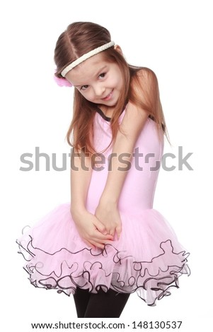 Smiling little girl in a tutu dancing - stock photo