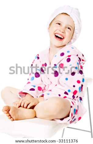 Smiling little girl in pink bathrobe after a bath - stock photo