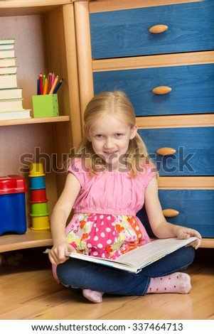 smiling little girl is reading at her room - stock photo