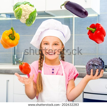 smiling little girl juggle vegetables home in the kitchen - stock photo