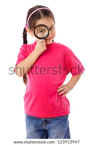 Smiling little girl looking through a magnifying glass, isolated on white - stock photo