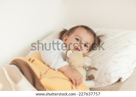 Smiling little girl  lying on her bed hugging her favourite soft plush toy tightly to her chest. - stock photo