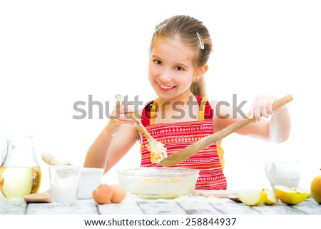 smiling little girl making dough  on a white background - stock photo