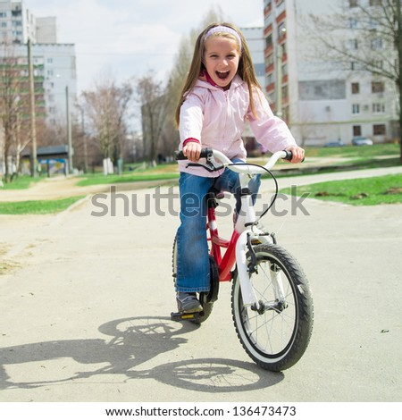 Smiling little girl on a bicycle in park - stock photo