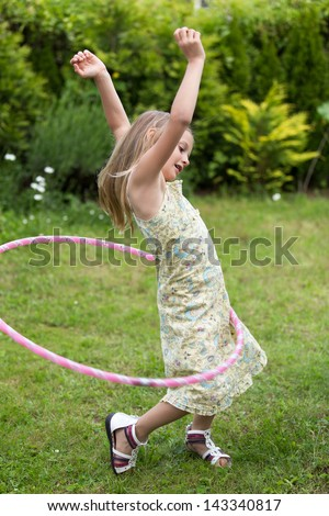 Smiling little girl playing with hula hoop in her garden. - stock photo