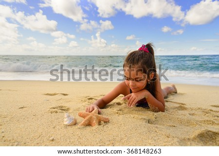 smiling little girl plays with a starfish on the beach on a summer day - stock photo