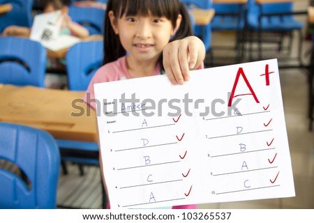 smiling little girl showing exam paper with a plus in the classroom - stock photo