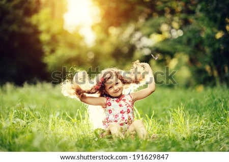 smiling little girl sitting on green grass with butterfly - stock photo