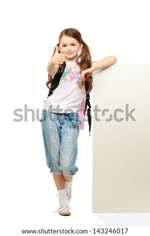Smiling little girl standing with books and holding empty white board - stock photo