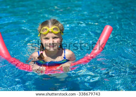 Smiling little girl swimming with a pink foam noodle in a pool while on summer vacation - stock photo