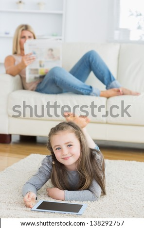 Smiling little girl using tablet on living room floor while her mother is reading newspaper on the couch - stock photo