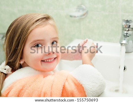 Smiling little girl washing hands in bathroom  - stock photo