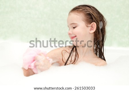 Smiling little girl washing in bath with bast - stock photo