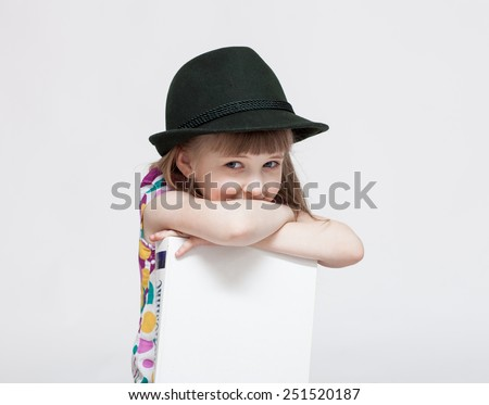 Smiling little girl with a big book, white background - stock photo