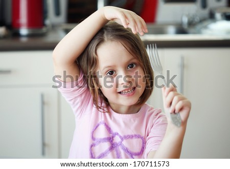 smiling little girl with a fork - stock photo