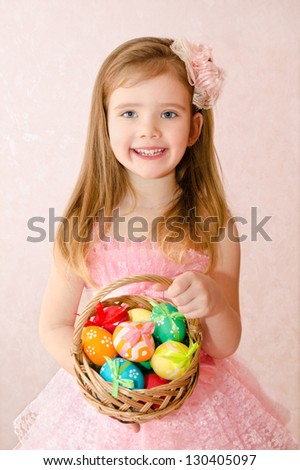 Smiling little girl with basket full of colorful easter eggs - stock photo