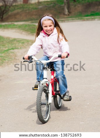 Smiling little girl with bicycle on road - stock photo