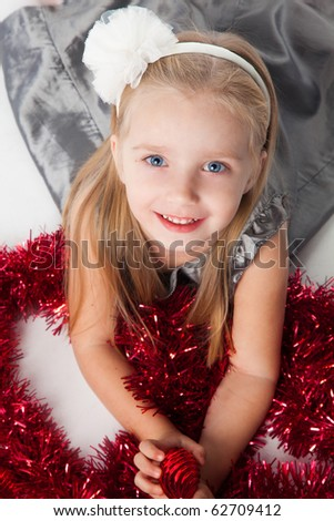 smiling  little girl with new year toys in grey dress - stock photo