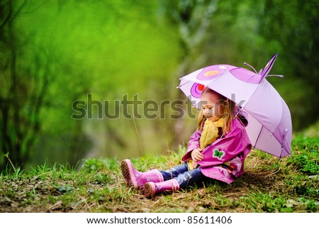 smiling little girl with umbrella in raincoat and boots outdoor - stock photo