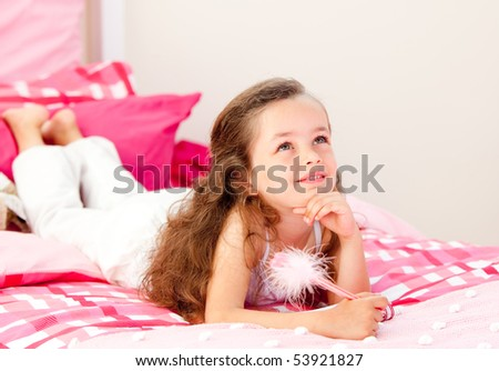 Smiling little girl writing on a notebook lying on her bed at home - stock photo