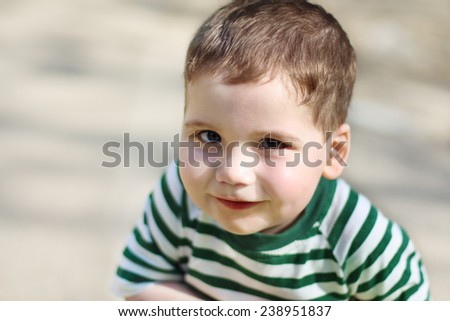 Smiling little handsome boy looks at camera in park. Shallow dof - stock photo