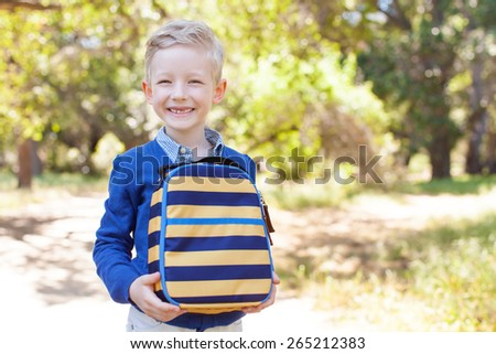 smiling little schoolboy holding lunchbag ready to go to school, back to school concept - stock photo